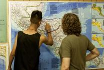 Unaccompanied minor migrants enjoy United Methodist Camp Colby in California. They point out their hometowns  on a large wall map. Photo courtesy of California-Pacific Conference.