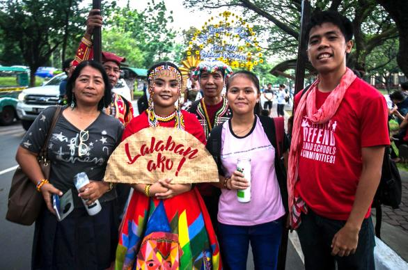 """Ofelia A. Cantor (left) stands with the """"Queen of Peace,"""" and others in a parade protesting tyranny by the government, May 26, at the University of the Philippines, Quezon City. United Methodist Women joined human rights defenders in a call to end martial law in the Philippines. Photo courtesy of Mark Z. Saludes."""