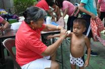 Ruth Arichea, wife of retired bishop Daniel C. Arichea Jr., puts powder on a child during Ligo Land, a ministry for street children in Manila, Philippines. The Central United Methodist Church event was held in conjunction with the 16th National Association of Filipino-American United Methodists Convocation 2018, which was held at the church. Photo courtesy of Aquilino Javier.