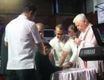 Bishop Daniel Arichea Jr. offers a prayer for Reynato S. Puno, kneeling, as other Filipino bishops and district superintendents lay hands on the former chief justice at a prayer gathering March 22 at Puno United Methodist Church in Diliman, Quezon City, Philippines. Puno, a United Methodist, was chosen by Philippines President Rodrigo Duterte to lead a Consultative Committee for Charter Change. Photo by Gladys Mangiduyos, UMNS.