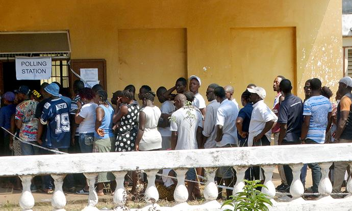 People stand in line to vote in multitier elections on March 7, 2018, outside The Great Hall of the Milton Margai College of Education and Technology at Goderich in rural Freetown, Sierra Leone. A runoff election for president will take place March 27 after no clear winner emerged on March 7. Photo by Phileas Jusu, UMNS.