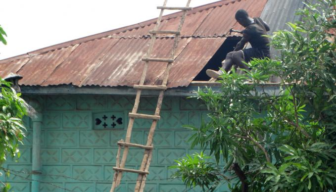 A carpenter repairs a roof in Bo, Sierra Leone, following a storm that destroyed many buildings and left much of the city without power. Photo by Phileas Jusu, UMNS.