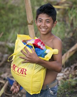 A young boy leaves a food distribution by the United Methodist Committee on Relief carrying food for his family following Typhoon Haiyan in Dagami, Philippines. Photo by Mike DuBose, UMNS