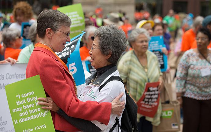 Harriett Jane Olson (left), United Methodist Women chief executive officer, greets Kyung Za Kim during a rally for a fair living wage on the steps of the Ohio Statehouse in Columbus during the United Methodist Women Assembly 2018. Kim is a previous national president of the organization. Photo by Mike DuBose, UMNS.