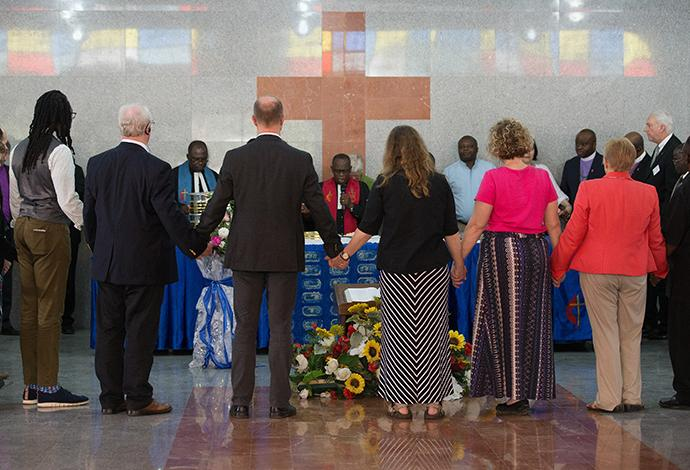 Members of the United Methodist Standing Committee on Central Conference Matters gather for Communion at Canaan United Methodist Church in Abidjan, Côte d'Ivoire. Consecrating the elements is Bishop Benjamin Boni (center). Photo by Mike DuBose, UMNS.