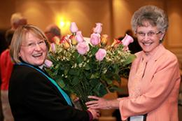 Bishop Rosemarie Wenner (left) of the Germany Area receives roses from Bishop Peggy Johnson of the Philadelphia Area following the