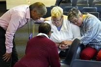 Bishops pray with representatives from the unofficial advocacy group Love Prevails during the Council of Bishops meeting in November. The group asked the bishops to address the LGBTQ community. Pictured from left are Bishops Grant Hagiya and Linda Lee praying with the Rev. Amy DeLong and her wife, Val Zellmer. Photo by the Rev. Maidstone Mulenga, Council of Bishops.