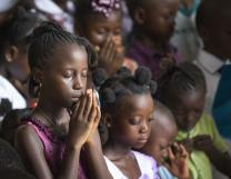Children pray in Sierra Leone prior to net distribution. Photo by Mike DuBose, UMNS.