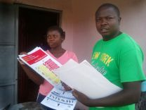 Christian Zigbuo (right) works to distribute printed information to educate people in Liberia  about the Ebola virus.