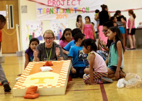 Project Transformation is an eight-week summer camp held in churches creating bonds between the interns and the children they serve. Challye Hays laughs with children as they play corn hole in the gym at Antioch United Methodist Church.