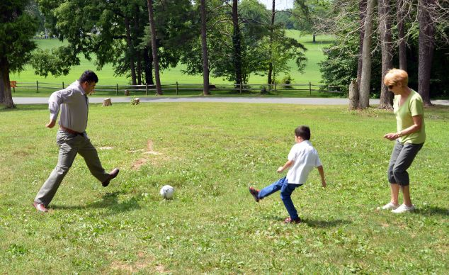 Hameed (left) and his son, Rawof, kick a soccer ball with church friend Margene Sims.