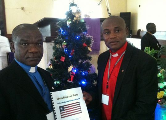 The Rev. Samuel Brown, superintendent of the Monrovia District, and the Rev. Alex Harmon pose with an Ebola Disease Facts Booklet during a book distribution at Tubman United Methodist Church in Paynesville outside of Monrovia. Photo by Julu Swen, UMNS