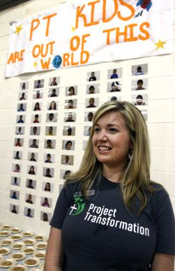 Courtney Aldrich, director with Project Transformation, stands by a wall showing photos of the kids in the Project Transformation camp at Antioch United Methodist Church.