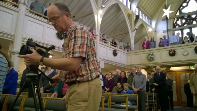 Steven Benson, an Anglican priest and TV producer, shoots video of the congregation at Knutsford Methodist Church in Cheshire, England, to share with the United Methodist Erlöserkirche (Church of the Redeemer) in Bremen, Germany, on Christmas Eve. Photo by Kathleen LaCameraUMNS