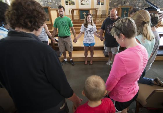 The Rev. Paul Bonner (at rear in green shirt) leads a prayer service at Christ United Methodist Church in Franklin, Tenn., to lift up those facing the Ebola crisis in West Africa. Bonner, youth minister at the church, helped lead a 2013 mission team to Sierra Leone.