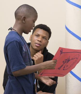 Teen volunteer Tra'Sean, right, encourages 6th-grader J.B. to explain his drawing at the Freedom School at Gordon Memorial United Methodist Church in Nashville, Tenn.