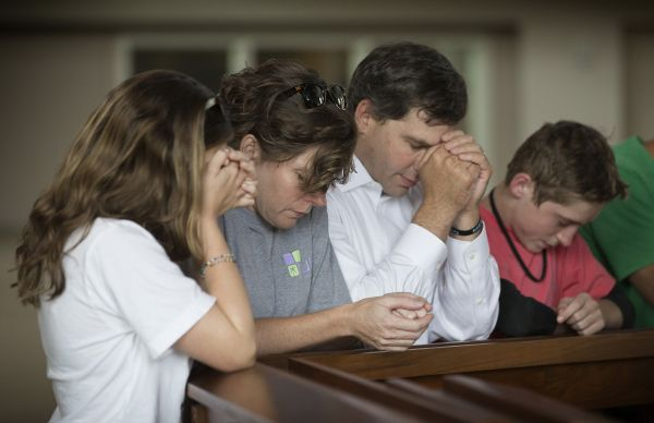 Members of the Bonn family pray during a service at Christ United Methodist Church in Franklin, Tenn., to lift up those facing the Ebola crisis in West Africa. From left are: Ashley, Debbie, Danny and Miles.