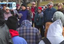 Members of AfterHours Denver sing hymns with the homeless in Civic Center Park on Christmas Day 2014. Video image by Deniger Stories for AH Denver.
