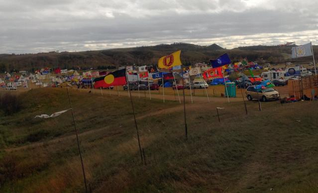 A line of flags marks a campsite near Cannon Ball, N.D., occupied by members of the Standing Rock Sioux Tribe as a base to protest the Dakota Access Pipeline. Photo by Erin Hawkins, United Methodist Commission on Religion and Race.