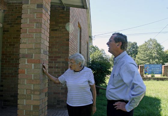 Ida Mae Nutt, the last surviving member of Carthage United Methodist Church, shows the Rev. James Batts some water damage on the brick building. The members of the four churches in the Carthage charge talked about closing the church earlier this year, but Nutt and the others decided to keep the building open for worship once a month. Nutt, with help from Matthews, takes care of the building. Photo by Heather Hahn, UMNS.