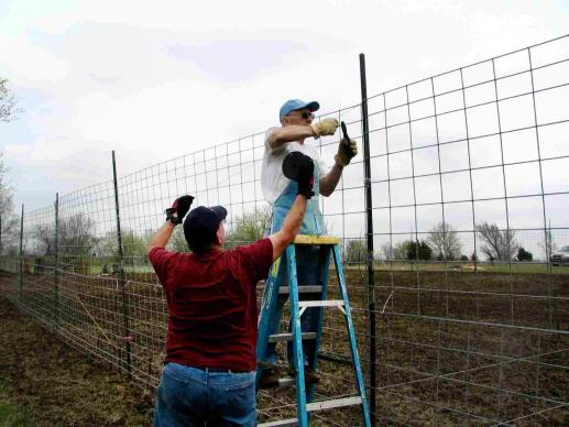 "Volunteers with Bartlesville First Church prepare the fencing for their community garden in order to ""keep the critters out."" The project started as a 2009 Change the World project."
