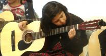 Isabella Barco, 7, practices a D chord in guitar class at Christ's Foundry United Methodist Church in Dallas.