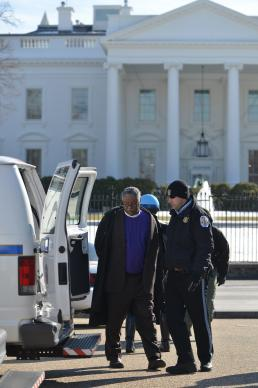 Police load Bishop Julius Trimble on a transport van after arresting him at a prayer vigil at the White House in support of progress on immigration reform and an end to deportations. Washington, DC, on Feb. 17. Photo by Jay Mallin, UMNS.