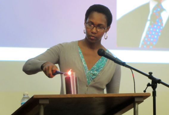 The Rev. Dountonia Slack lights a candle remembering victims of domestic abuse during an Oct. 2-4 conference hosted by St. Luke's United Methodist Church in Indianapolis.