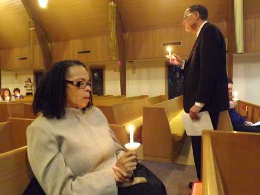 The Rev. Dan Flanagan (standing) helps lead a prayer service for Dr. Martin Salia at Hanscom Park United Methodist Church in Omaha, Neb., Nov. 16. Salia, chief medical officer and surgeon at United Methodist Kissy Hospital in Freetown, Sierra Leone, died at Nebraska Medical Center Nov. 17 from Ebola. Seated is the Rev. Portia Cavitt.