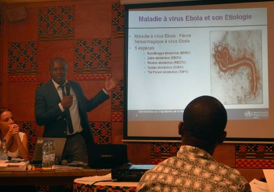 World Health Organization's Dr. Anderson Lath speaks during a BBC Media Action workshop in emergency communication, Nov. 26-27, in Abidjan. On the screen is an enlargement of the Ebola virus. Photo by Isaac Broune, UMNS
