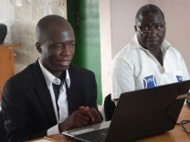 Ehui Eboua, infectious and tropical diseases specialist, displays his PowerPoint while teaching the staff of the Voice of Hope Radio about the Ebola threat. Seated next to him is M. Hyacinthe Besse, Côte d'Ivoire United Methodist Health Board's coordinator. Photo by Isaac Broune, UMNS