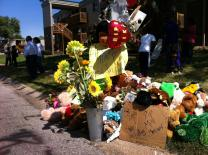 An impromptu memorial marks the area where Michael Brown was killed in Ferguson, Mo. Photo by Matt Miofsky.