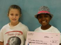 We Cancerve founder Grace Callwood and volunteer Addison Simpler hold a check from We Cancerve.