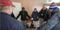The Rev. Tom Hazelwood (second from right), of The United Methodist Committee on Relief leads a prayer at a home damaged by flood waters from Hurricane Sandy in Massapequa, N.Y. Photo by Mike DuBose, UMNS.