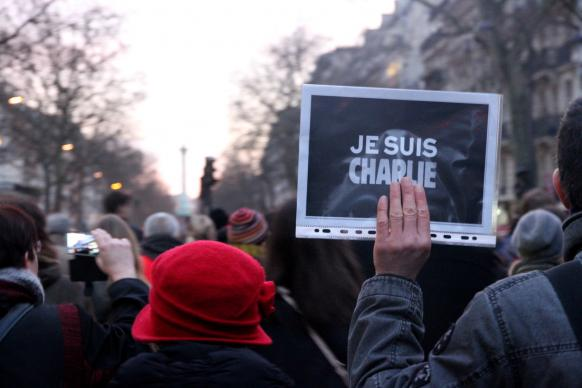 "Parisians gather in solidarity holding signs reading, ""Je suis Charlie."" Photo by Maya-Anaïs Yataghène, flickr creative commons."