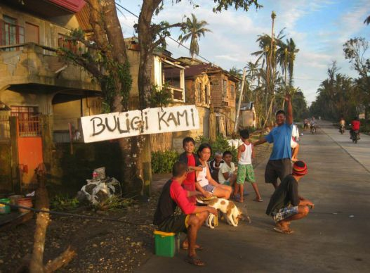 "After Typhoon Hagupit, a family in Taft in the province of Eastern Samar sits by a sign that says buligi kami, which translates ""Help us please."" Photo by Marlon Paano Lasaca"