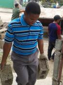 Rev. Norges Rodriguez Cascaret of the San Luis church in Santiago de Cuba carries cement blocks while assisting workers in construction of new UMCOR-funded homes. Photo by Greg Forrester, courtesy of UMCOR.