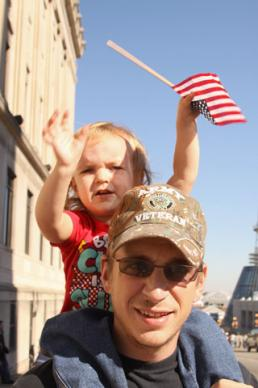 Cadence Cobb, 2, waves an American flag as she rides on the shoulders of her dad, U.S. Army veteran A.J. Cobb