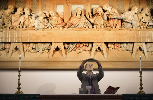 "The Rev. Edgardo Colón-Emeric blesses the elements of Holy Communion in front of a woodcarving of Leonardo da Vinci's ""The Last Supper"" at the Upper Room Chapel in Nashville, Tenn. A UMNS photo by Mike DuBose."