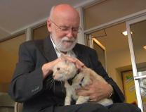 Joe Hirsch prays over Franz the cat during a pet blessing. Video image by Clay Kisker, United Methodist Communications.