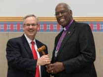 Bishop Bruce R. Ough (left) receives the gavel as incoming president of the United Methodist Council of Bishops from outgoing president Warner H. Brown, Jr. during the 2016 General Conference in Portland, Ore.