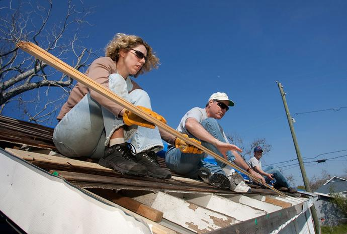 Volunteers from Christ Church United Methodist in New York repair a roof damaged by winds from Hurricane Katrina in Biloxi, Miss., in 2006. From left are: Marsha Askins, the Rev. Richard Allen, and Chris Andrews. Collaborative relationships established between faith-based, secular and governmental groups in the recovery from Hurricane Katrina have changed the face of local disaster response, relief officials said. File photo by Mike DuBose, UMNS.