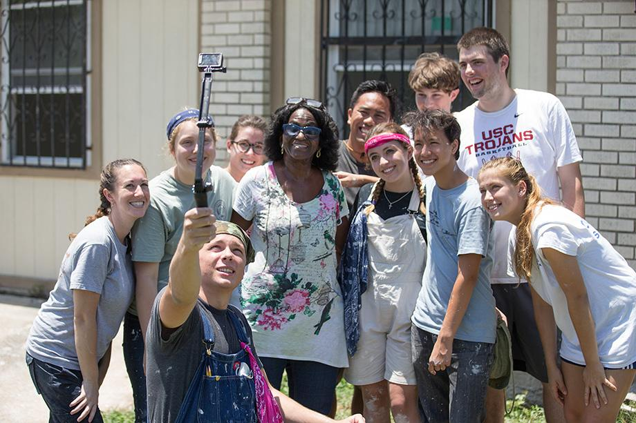 Sam Guyette (foreground) holds a camera on a selfie stick for a group photo with volunteers from First United Methodist Church of Santa Monica, Calif., and Betty Johnson at her home in New Orleans' Upper 9th Ward. Repairs to Johnson's home were nearing completion almost 10 years after Hurricane Katrina devastated the Gulf Coast. Photo by Mike DuBose, UMNS.