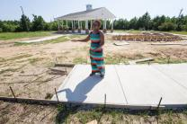 Dorothy Booker walks along the incomplete outdoor prayer pavilion at historic Gulfside Assembly in Waveland, Miss. Hurricane Katrina destroyed every building on the grounds in 2005. Photo by Mike DuBose, UMNS.