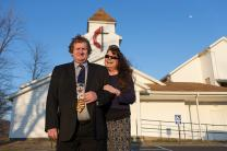 The Rev. Jamie Sprague and his wife Kay stand in front of Kanawha Chapel United Methodist Church in Davisville, W.Va., where Sprague serves as a licensed local pastor. Photo by Mike DuBose, UMNS.