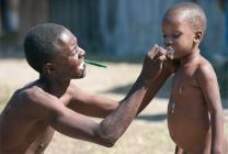 A father helps his son with basic hygiene at the camp where they are staying in Leogane, Haiti.