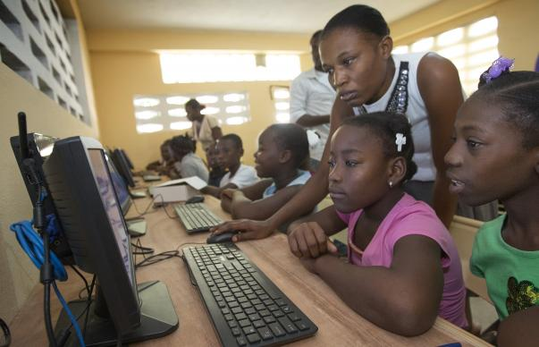 Teacher Sylné Guerdy works with students in the Thomas Food Project's computer lab in Haiti.