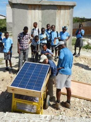 A team from the Thomas Food Project hooks up a solar-powered cart used to charge laptops and mobile phones and run water purifiers for cooking and drinking.