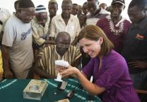 Maeghan Orton (right) explores a solar cell phone charger with Paramount Chief Joseph Kposowa (seated, center) in Bumpe village near Bo, Sierra Leone, about mobile phone technology. Photo by Mike DuBose, UMNS