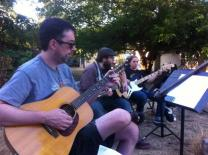 The Rev. Jeff Lowery (left) plays guitar during an outdoor worship service of Sellwood Faith Community in Portland, Ore. Sellwood is among the new church starts in Portland, Ore., drawing people into Christian community. Photo courtesy of the Rev. Eilidh Lowery.